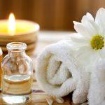 Aromaterápia eszközei: illóolajak üvegcsékben, illatmécses, puha törülköző, friss virág.