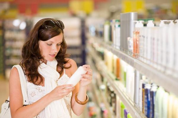 Egy fiatal nő olvassa egy drogériában a terméken lévő cimkét, mely az összetevőket tartalmazza.