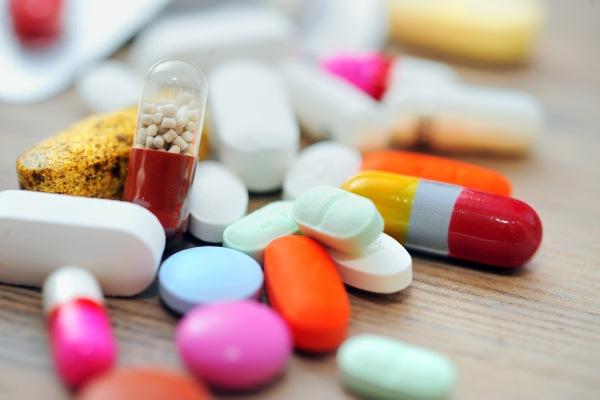 Különféle formájú és színű gyógyszerek, kapszulák egy rakáson.