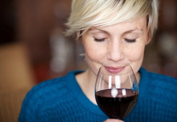 Szőke hajú nő kék pulóverben egy pohár vörösbort készül inni.