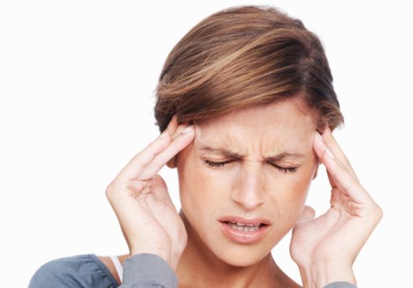 Migrénnel küzdő nő két kézzel fogja fájó halántékát.