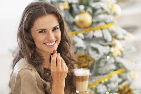 Habos kávé mellé bonbont csemegéz egy dekoratív hölgy a karácsonyfa előtt.