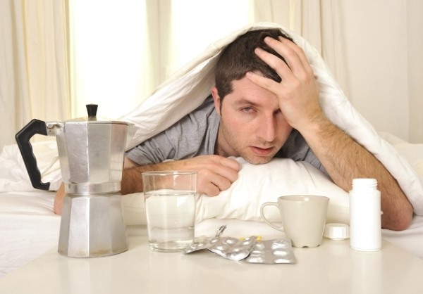 Másnapos férfi néz ki a paplan alól, előtte az asztalon kávé, víz és gyógyszerek.