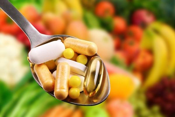 Evőkanál teli vitaminokkal, étrend-kiegészítőkkel. A háttérben sok-sok gyümölcs és zöldség.