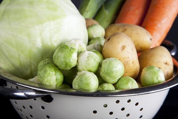 Zománcozott szűrőben téli zöldségek: káposzta, kelbimbó, sárgarépa és krumpli.