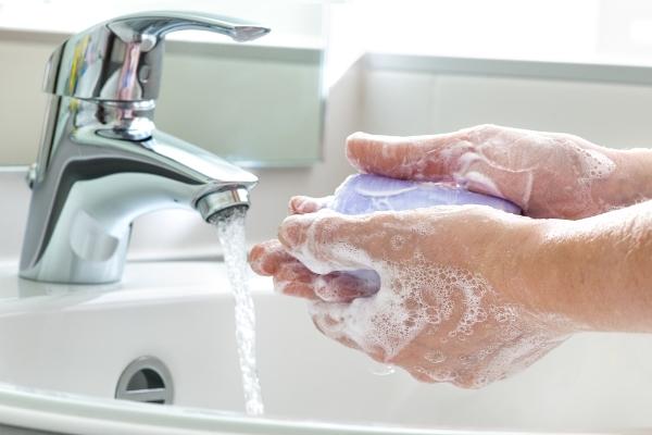 Lila színű szappannal mosnak kezet folyó víz alatt.
