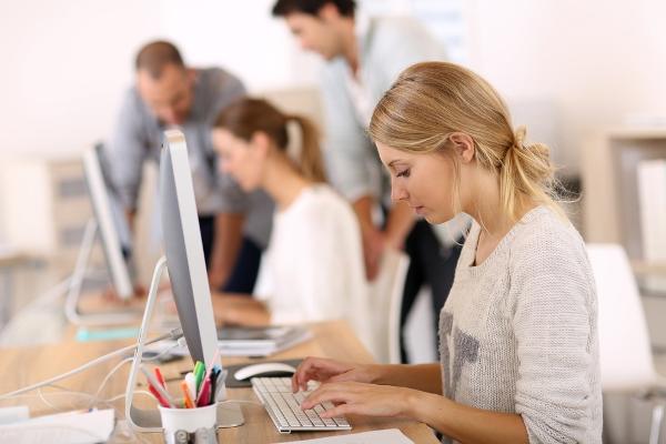 Irodában iMac előtt ül több hölgy, gépelnek a klaviatúrán.