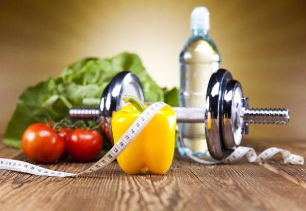 Egészséges életmód eszközei: zöldségek, súlyzó, ásványvíz és a diétára utaló centiméter.