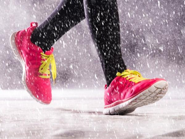 Hóesésben egy futó lába, rajta fekete futónadrág és pink színű sportcipő citromsárga fűzővel.