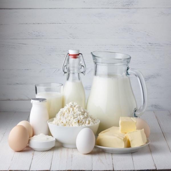 Tojás, túró, vaj, joghurt, kefír, író és friss tej az asztalon.