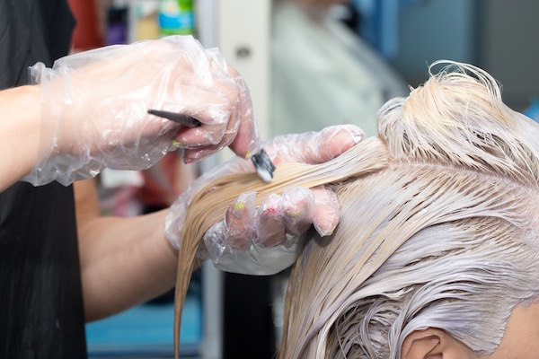 Szőkére festik egy hölgy haját egy fodrászszalonban.