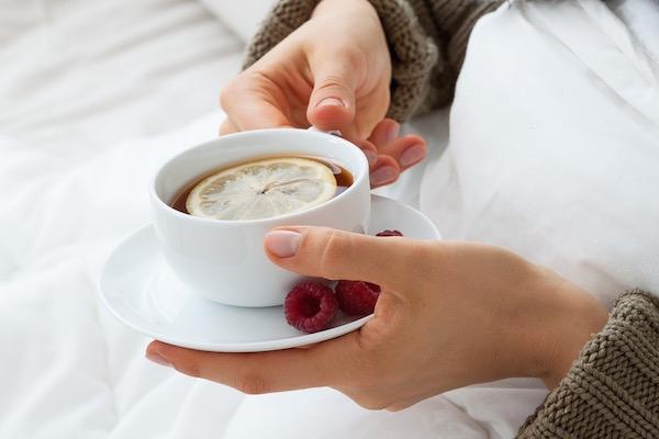 Ágyban fekvő nő citromos teát fog kezében, a tányéron pár szem málnával.