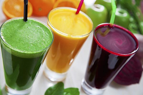 Frissen préselt gyümölcs- és zöldséglevek üvegpohárban, mögöttük az alapanyag: narancs, zöldalma és cékla.