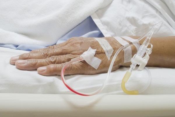 Kórházi ágyon fekvő hölgy kezéből állnak ki mindenféle csövek: infúzió, kanül.
