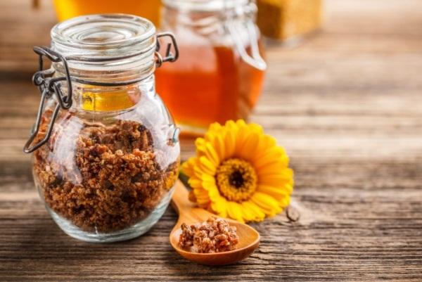 Propolisz egy zárható, csatos üvegben és egy darabka belőle fakanálon egy sárga virág mellett. A háttérben különféle méztermékek.