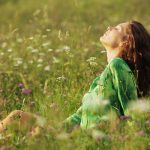 Vadvirágokkal teli réten ül a fűben egy vörös hajú lány, közben a napfénybe néz becsukott szemmel, és mélyeket lélegez.