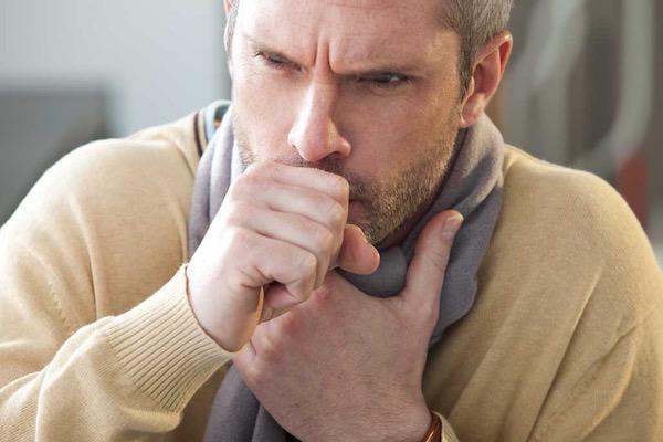 Középkorú férfi drapp pulóverben erősen köhög, a nyakában szürke sál.