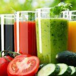 Frissen facsart színes zöldség- és gyümölcslevek, mellettük az alapanyagok: cékla, paradicsom és uborka.