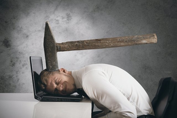 Fiatal üzletember laptopjára borul, miközben egy óriás kalapács fejen üti.