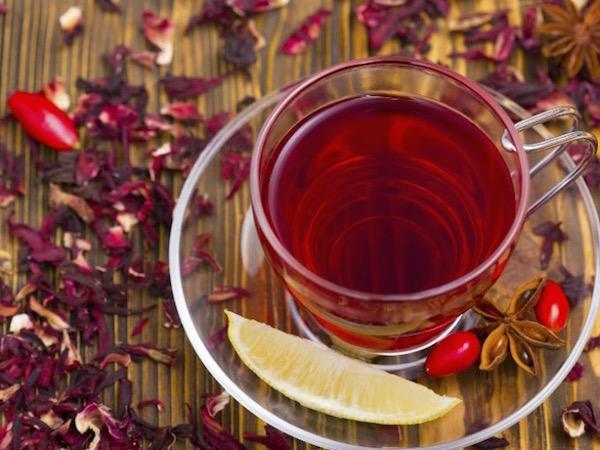 Vérvörös hibiszkusztea átlátszó pohárban, mellette citromgerezd.