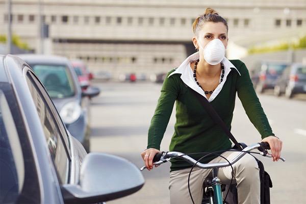 Szájmaszkban kerékpározik egy fiatal nő Budapest forgalmas utcáján.