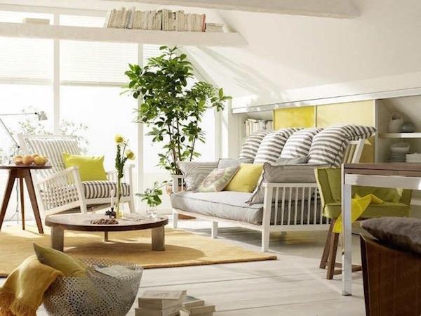 Napfényes tetőtéri szoba kellemes színekkel, az ablaknál óriás zöld növénnyel.