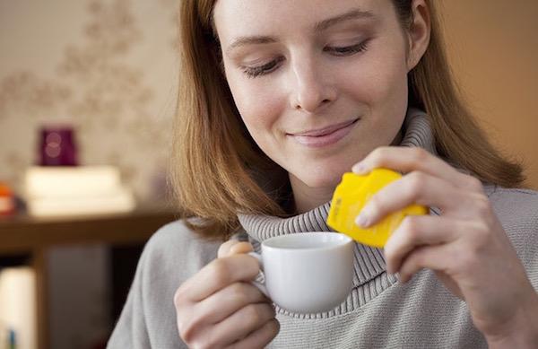 Fiatal nő a kávéjába édesítőszert adagol.