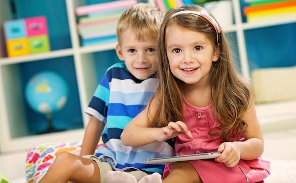 Ksilány játszik egy tablettel, mellette ül egy kisfiú, mindketten szembenéznek a kamerával.