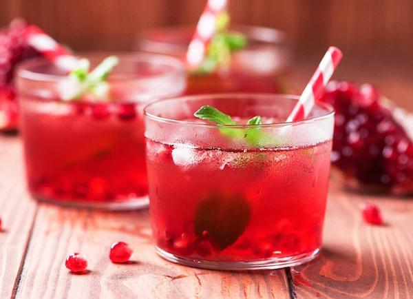 Gránátalmát tartalmazó frissítő, jéghideg ital mentalevélkékkel, szívószállal.