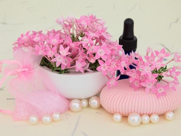 Verbéna apró virágai, mellette egy belőle készült szappan, fehér gyöngyök és illóolajas üvegcse.