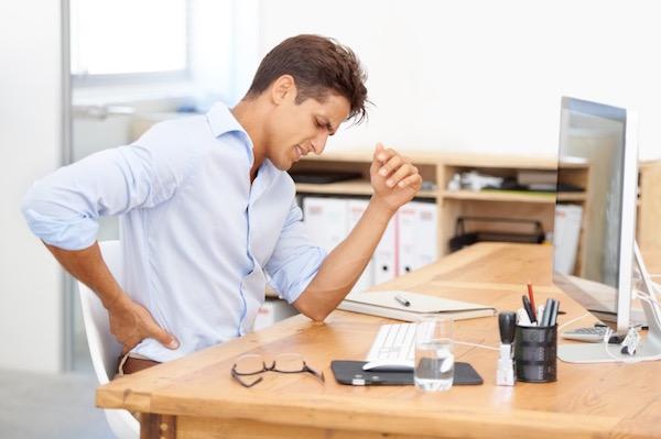 Fiatal férfi számítógépe előtt ülve fájlalja a derekát.