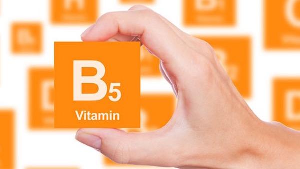 B5-vitamint ábrázoló narancssárga táblát tart egy női kéz.