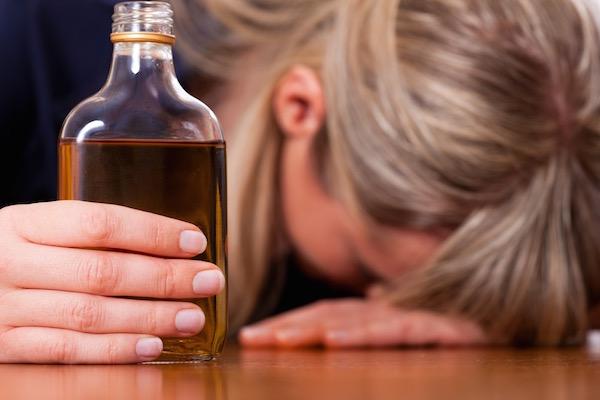 Kezében whiskys üveget tartó nő borul az asztalra, feje a kézfején pihen, túl sok italt fogyasztott.
