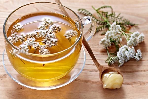 Cickafarkból készült gyógytea, mellette a cickafark virága és egy kis fakanálnyi méz.