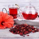 Hibiscus sabdariffa tűzpiros virága, mellette átlátszó üvegkancsóban és pohárban a belőle készült hibiszkusztea.