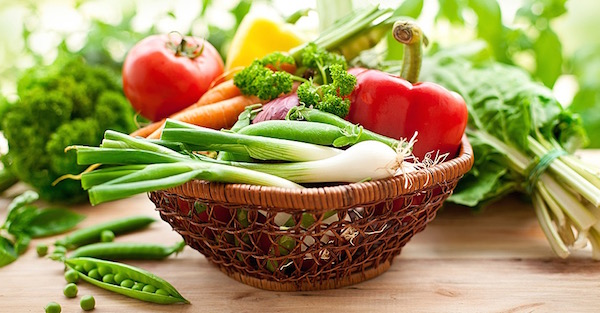 Friss zöldségek egy kis, fonott kosárkában és mellettük, az asztalon is.