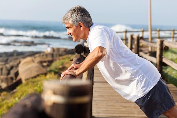 Sportos, idősebb férfi karját erősíti a tengerparti móló korlátjánál.
