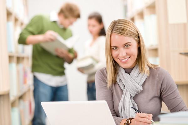 Könyvtárban ülő egyetemista lány laptopját nézve jegyzetel, a háttérben társai jegyzeteket, könyveket néznek.