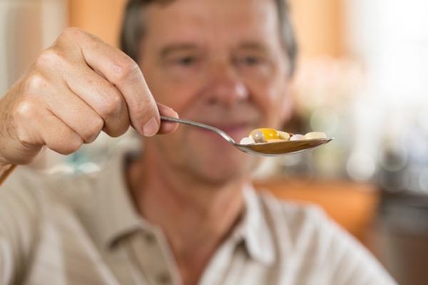 Idősebb férfi egy evőkanálnyi vitamint tart kezében.