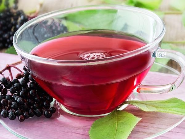 Fekete bodzából készült mélybordó színű tea üvegcsészében.