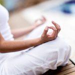 Fehér ruhában lévő, kezét térdére fektető meditáló hölgy, mutató- és hüvelykujja csin mudrában van.