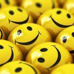 Sok nevető, smileyt ábrázoló citromsárga golyó egymás mellett.