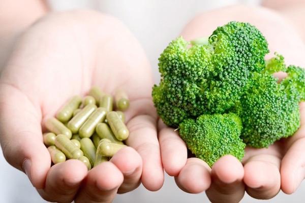 Két tenyér egymás mellé téve, egyikben a friss vitamint szimbolizáló brokkoli, másikban zöld étrend-kiegészítő kapszulák.