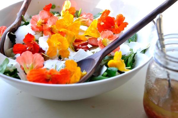 Különleges saláta zöld növényekből, eperből és kerti sarkantyúka színes virágaiból.