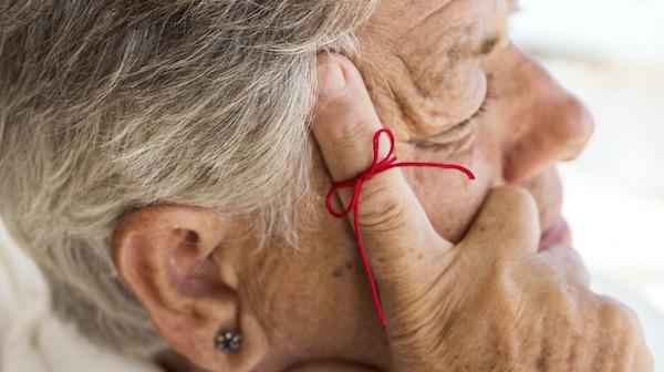 Idősebb hölgy fejét kezén támasztja, mutatóujján piros fonálból kötött emlékeztetőjel.