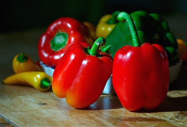 Különféle színű és formájú paprikák egymás mellett az asztalon.