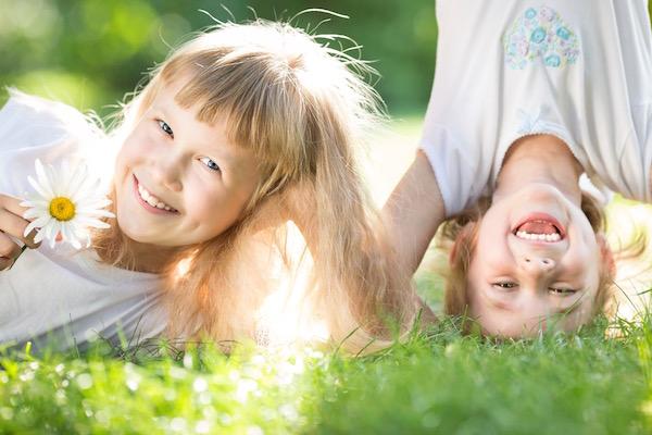 Két kislány a réten játszik, az egyik kezében fehér virág, a másik fejenállást csinál a fűben, közben mosolyognak mindketten.