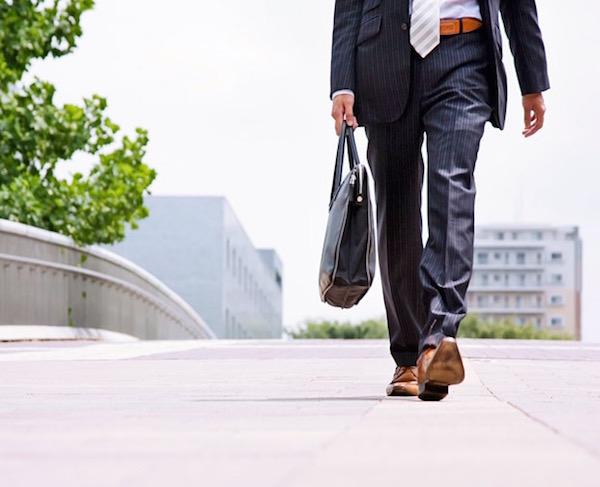 Öltönyös férfi laptoptáskával a kezében gyalogosan munkába igyekszik.