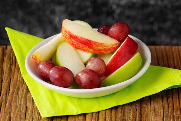 Zöld szalvétán fehér tányér, rajta almaszeletek és szőlőszemek.