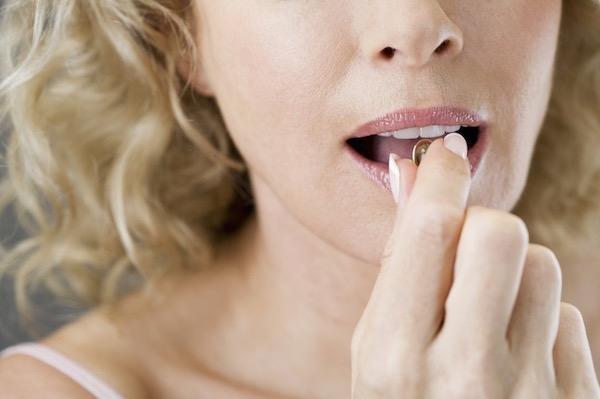Omega-3 zsírsavat tartalmazó gélkapszulát vesz szájába egy változókorban lévő nő.